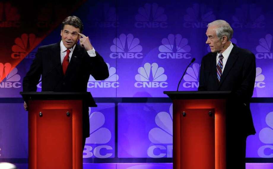 Republican presidential candidate  Texas Gov. Rick Perry (left) ponders yet another question at Wednesday's GOP debate in Auburn Hills, Mich. Yes, Perry flubbed a question, but was anybody else there much more coherent? Photo: Paul Sancy, Associated Press
