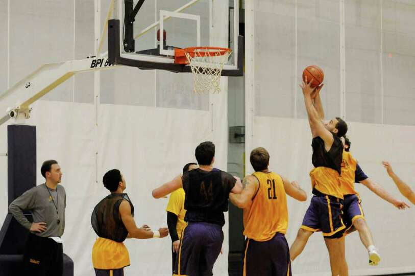 University at Albany head men's basketball coach Will Brown,left, watches his team practice in Alban