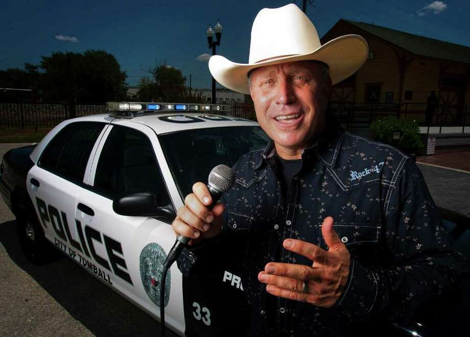 """Tomball Police Chief Robert Hauck poses for a portrait while singing country music in front of a police cruiser on Wednesday, August 3, 2011 in Tomball. Hauck moved to Tomball from Los Angeles in June 2008, """"I fell in love with this place,"""" said Hauck, who sings country and gospel music at church and in the community. He won Tomball's American Country Idol contest. ( Patrick T. Fallon / Houston Chronicle ) Photo: Patrick T Fallon / © 2011 Houston Chronicle"""
