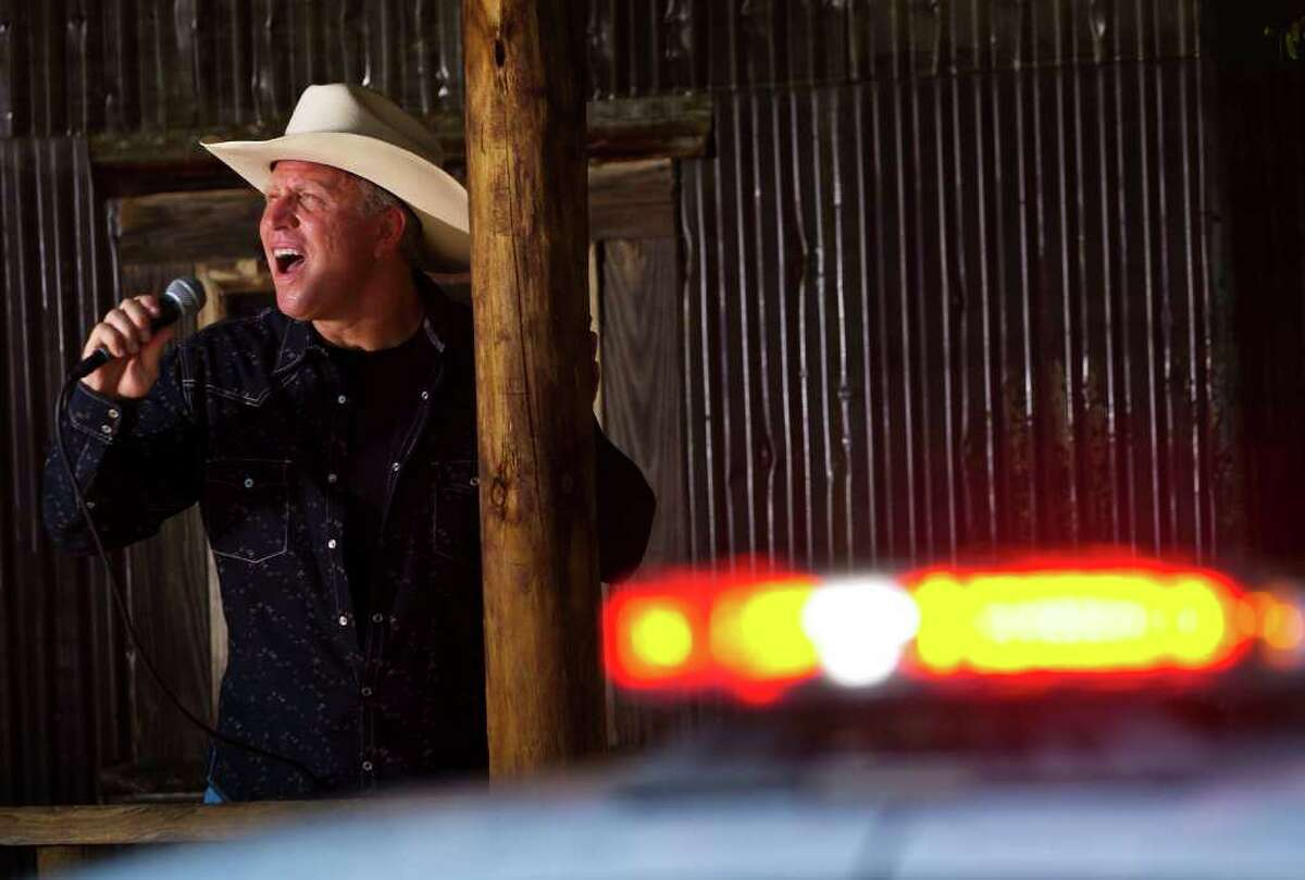 Tomball Police Chief Robert Hauck poses for a portrait while singing country music in front of a police cruiser on Wednesday, August 3, 2011 in Tomball. Hauck moved to Tomball from Los Angeles in June 2008,