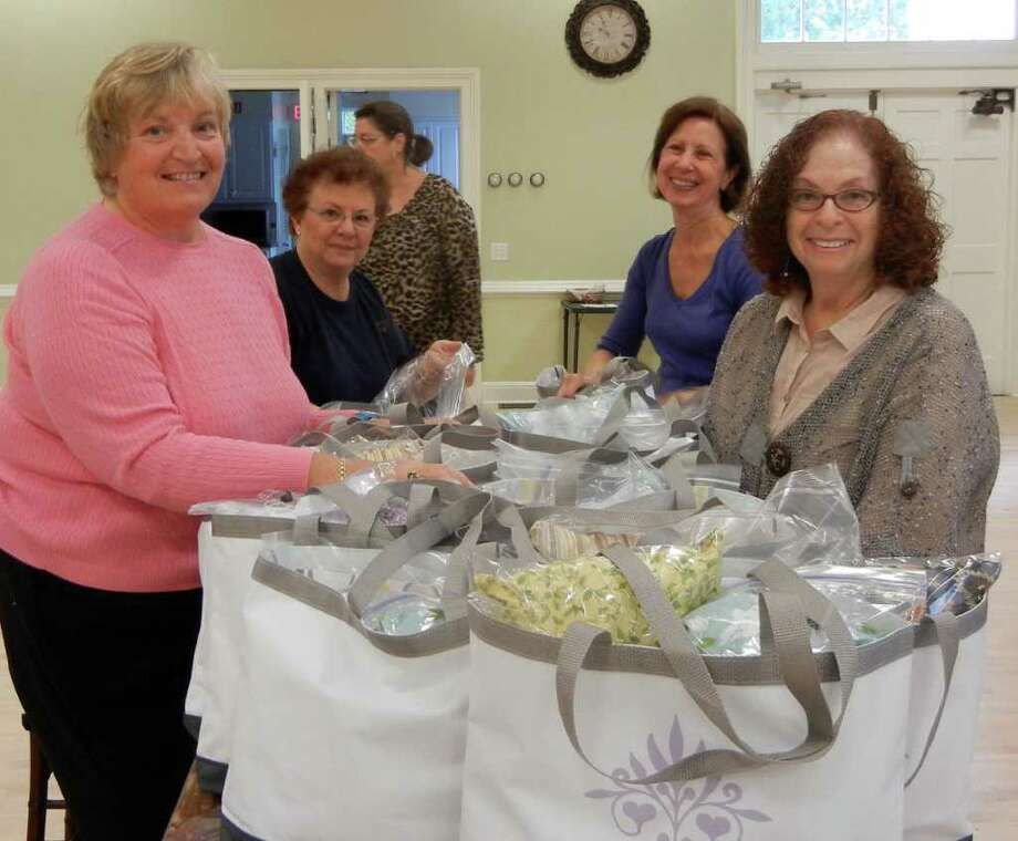 Volunteers from the Westport Woman's Club, left to right, Linda Amos, Diana Zaslow, Jo Calcagni and Audrey Rabinowitz pack and tie bags. Lisa Turnick of Necessities Inc. can be seen in the background. Photo: Contributed Photo