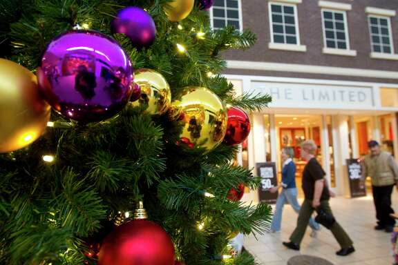 As the holiday season approaches, retailers are responding to the growth of online shopping by hiring more employees to work from home in online chat rooms, answering consumers' questions.  Shoppers at Memorial City Mall walk past a decorated Christmas tree as the holiday shopping season is getting started Wednesday, Nov. 3, 2010, in Houston. ( Johnny Hanson / Houston Chronicle )