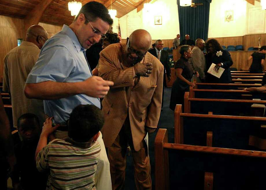Dr. Ron Karni shakes hands with his patient, the Rev. Albert Williams while his son Jacob, 4, attend during church services at the Salem Missionary Baptist Church in Independence Heights, Oct. 23, 2011.  The Rev. Albert Williams is back in the pulpit at Salem Missionary Baptist Church after a year of silence. He lost his voice to laryngeal cancer when his voice box had to be removed. But a second procedure, performed by Dr. Karni,  restored his ability to speak and be heard, much to the delight of his congregation. After the surgery he was able to lead silent devotions, but could not speak to his congregation -- or anyone else -- in any way. ( Karen Warren / Houston Chronicle ) Photo: Karen Warren / © 2011 Houston Chronicle