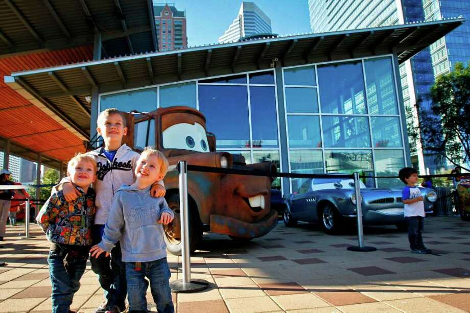 "Sam Cleminson, 6, (center) hugs his twin brothers Ethan, 3, (left) and Aaron, 3, as they have their photo taken in front of life-sized replicas of the characters ""Mater"" and ""Finn McMissile"" from the movie Cars 2 during the Disney/Pixar's CARS 2 State Farm Tour at Discovery Green, Thursday, Nov. 10, 2011, in Houston. Photo: Michael Paulsen, Houston Chronicle / © 2011 Houston Chronicle"