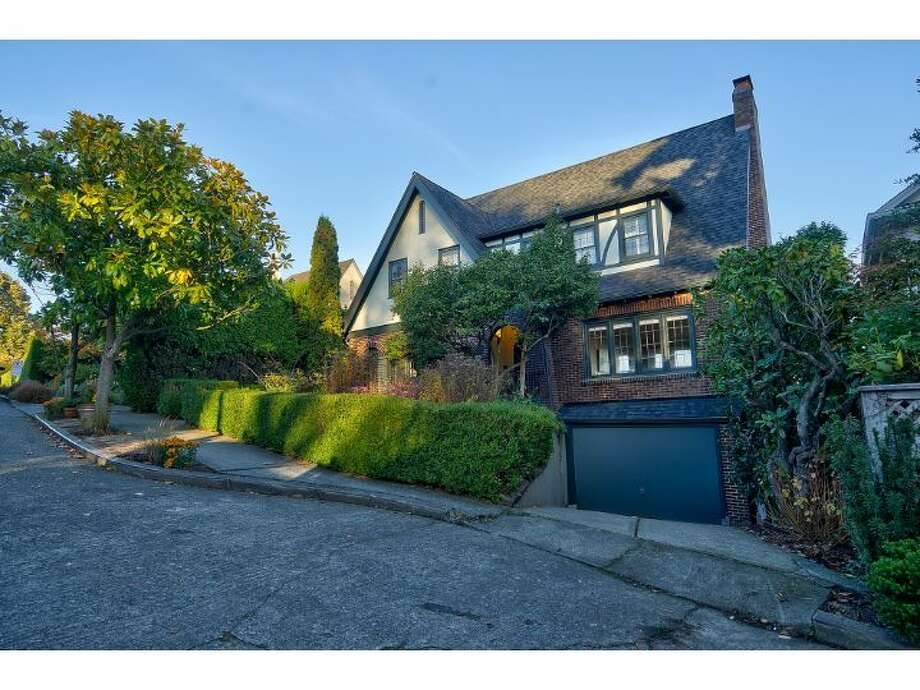 Here's an elegant brick Tudor in Seattle's classic Denny Blaine neighborhood, at 1516 40th Ave. The 3,460-square-foot house,  built in 1925, has four bedrooms, three bathrooms, coved ceilings, arched doorways, leaded glass, built-in cabinets a finished basement with a rec room and bar, two fireplaces and three decks, with views of Lake Washington and Mount Rainier. It sits on a 6,000-square-foot lot and is listed for $1.595 million. Photo: TallyAnn Carroll/Windermere Real Estate