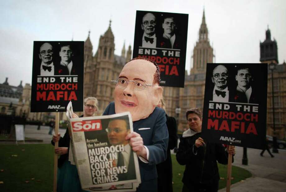 LONDON, ENGLAND - NOVEMBER 10: A member of the Avaaz protest group poses as James Murdoch reading a spoof newspaper near Parliament on November 10, 2011 in London, England. James Murdoch, Chairman and Chief Executive of News Corporation, owners of The News of The World newspaper, is facing further questions from Members of Parliament about phone hacking at the now closed newspaper.  (Photo by Peter Macdiarmid/Getty Images) *** BESTPIX *** Photo: Peter Macdiarmid / 2011 Getty Images