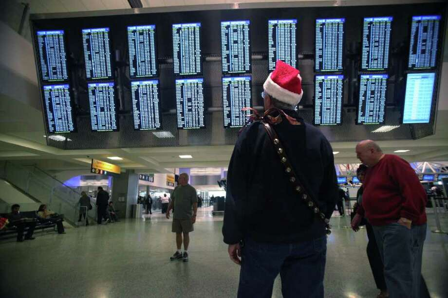 Mayra BeltrÁn : Chronicle File CHECKING IT TWICE: Jim Hunter looks for his son's flight last year during the holidays at Bush Intercontinental Airport. Photo: Mayra Beltran / Houston Chronicle