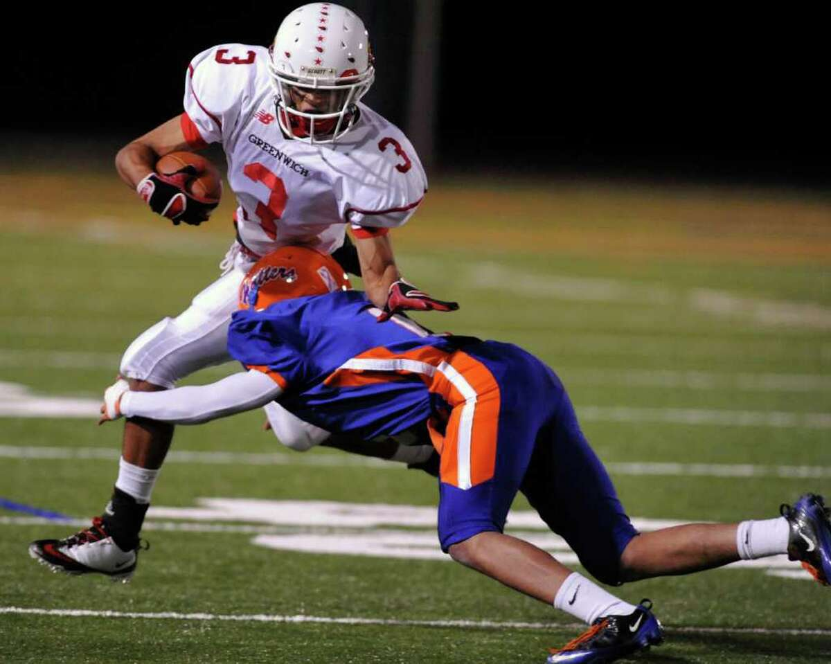 Greenwich's Joel Arroyo gets tackled by Danbury's Marcus Escribano during their game at Danbury High School on Thursday, Nov. 10, 2011.