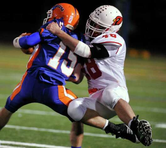 Danbury quarterback Garin Mooney is tackled by Greenwich's Shane Nastahowski during their game at Danbury High School on Thursday, Nov. 10, 2011. Photo: Jason Rearick / The News-Times