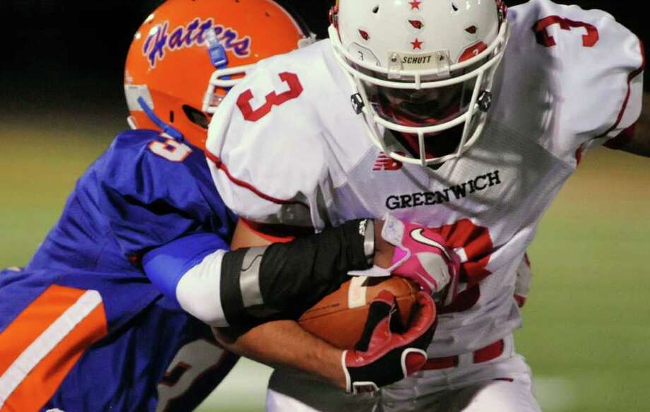 Danbury's James Harrington tries to bring down Greenwich's Joel Arroyo during their game at Danbury High School on Thursday, Nov. 10, 2011. Photo: Jason Rearick / The News-Times