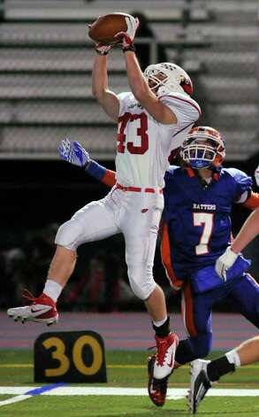 Greenwich's Mike Longo makes a leaping catch over Danbury's Corey Chaffee during their game at Danbury High School on Thursday, Nov. 10, 2011. Photo: Jason Rearick / The News-Times