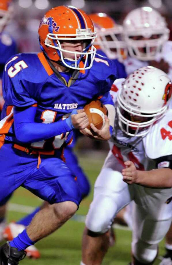 Danbury quarterback Garin Mooney runs with pressure from Greenwich's Shane Nastahowski during their game at Danbury High School on Thursday, Nov. 10, 2011. Photo: Jason Rearick / The News-Times