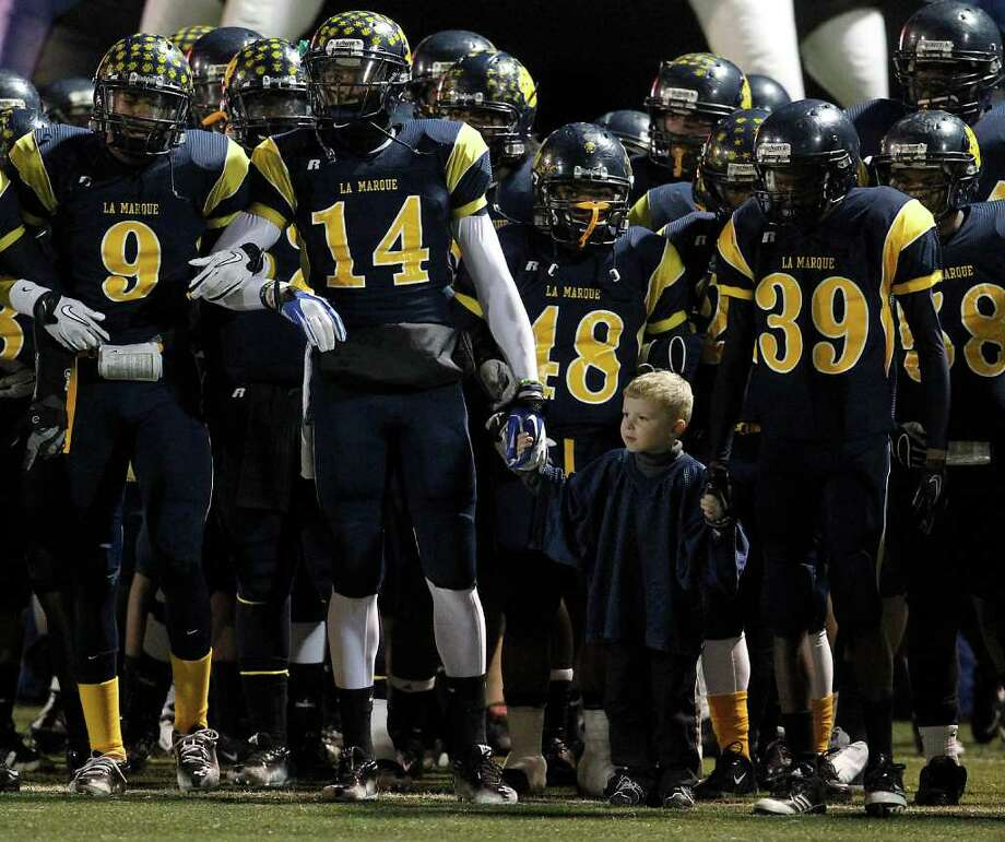 Ayden Lanius, 4, the offensive coordinator's son, holds hands with LaMarque players Brian Allen (14) and Derrick Lewis (39) before the start of the game. Photo: Karen Warren, Houston Chronicle / © 2011 Houston Chronicle