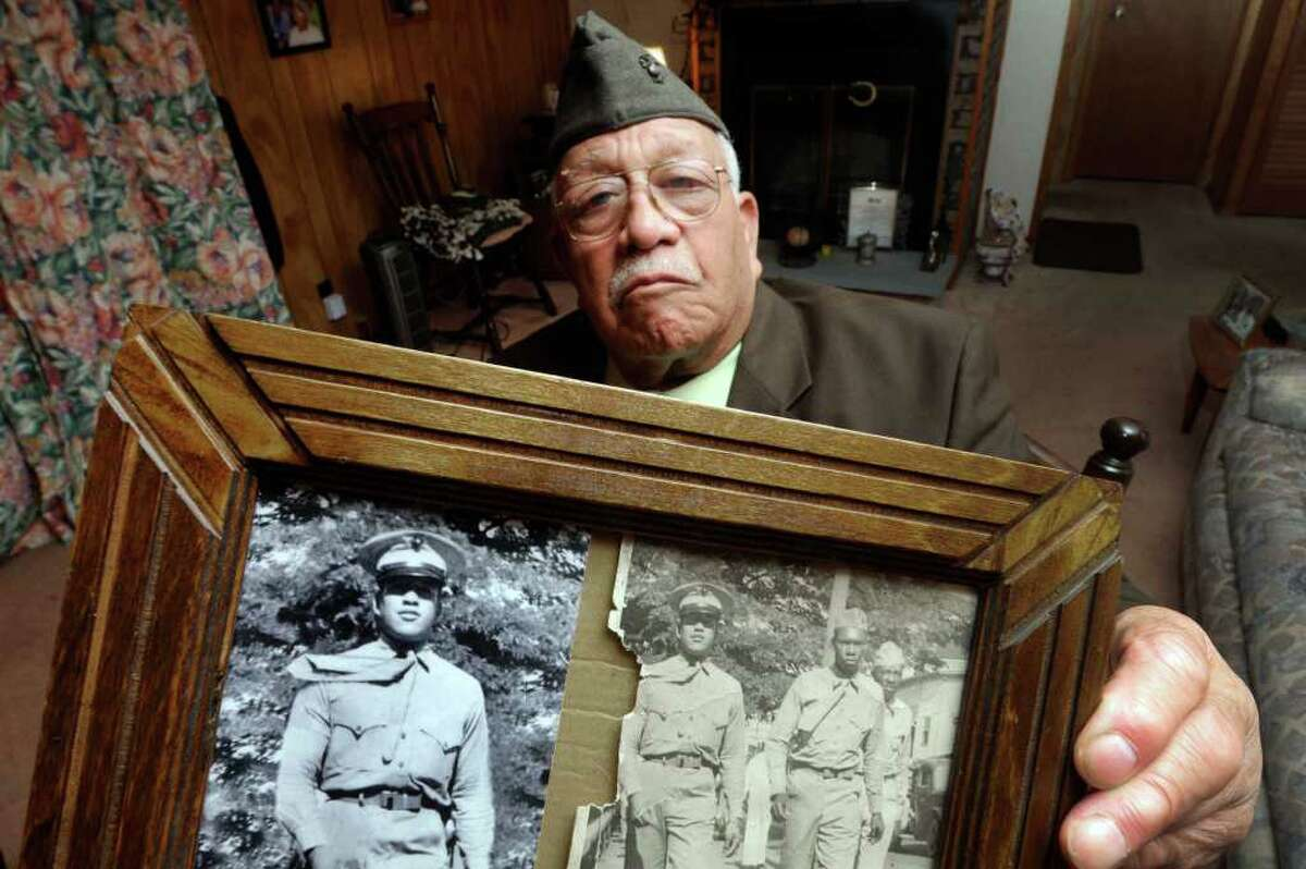 """World War II veteran Ambrose """"Cowboy"""" Anderson Jr. holds a photo from 1944 ,when he was a 18-year-old United States Marine, at his home in Gloversville, NY Thursday, Nov.10, 2011.( Michael P. Farrell/Times Union)"""