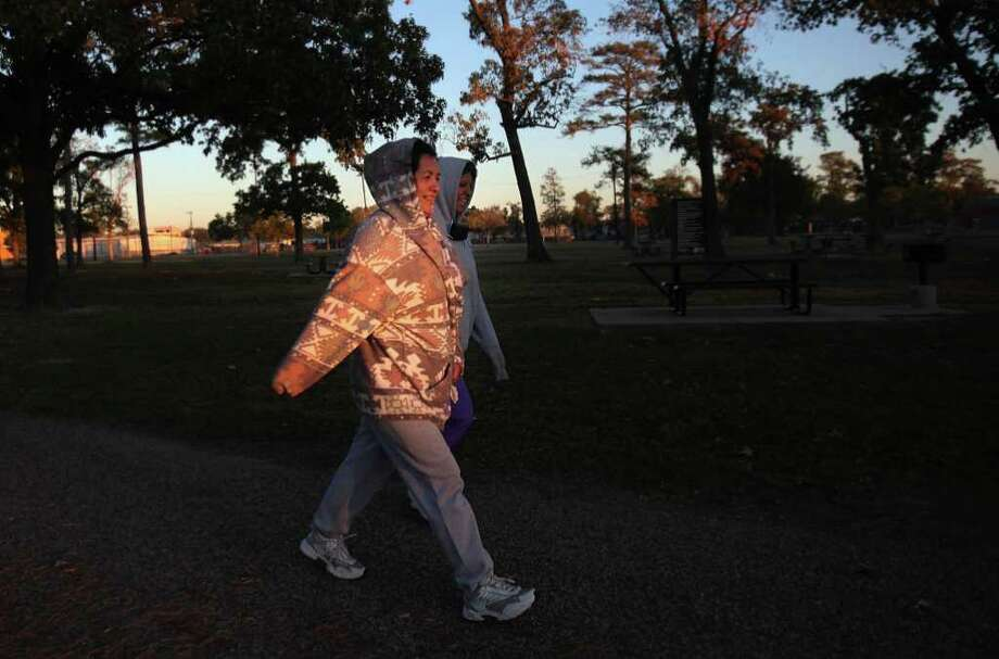 Sofia Rivera and Josefina Cisneros exercise by walking laps at Montie Beach Park despite the cold temperatures on Friday, Nov. 11, 2011, in Houston. Photo: Mayra Beltran, Houston Chronicle / © 2011 Houston Chronicle