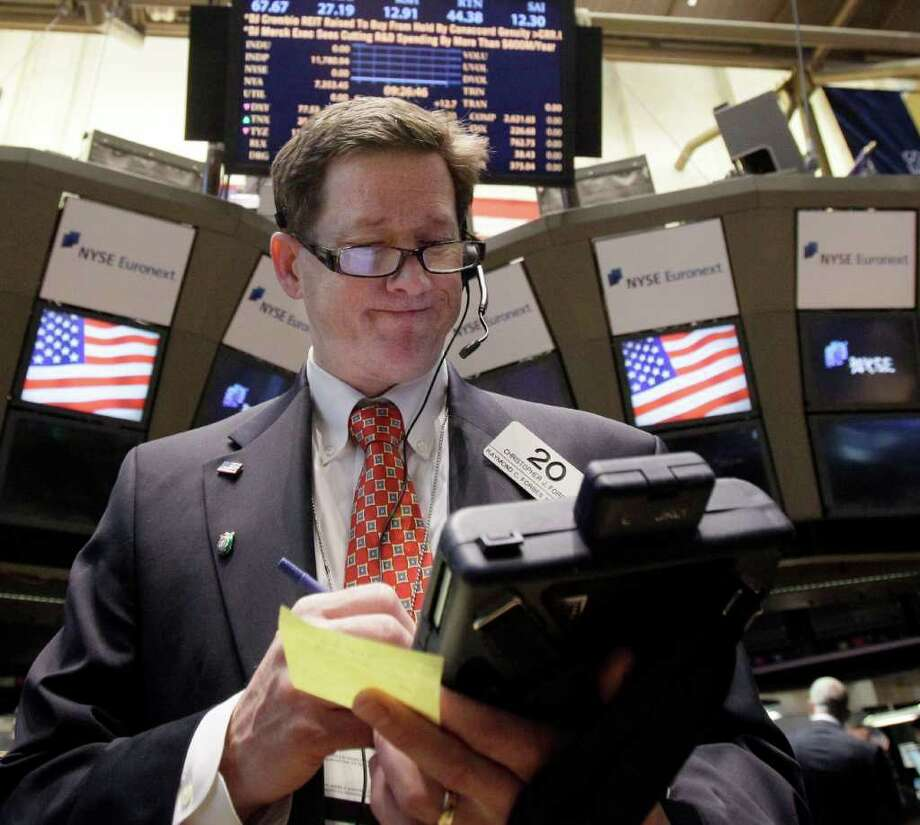In this Nov. 10, 2011 photo, trader Christopher Forbes works on the floor of the New York Stock Exchange. The prospect of new governments in Greece and Italy helped support market sentiment Friday, Nov. 11, 2011, at the end of a hugely-volatile week when investors fretted over the future of the euro currency and the outlook for the global economy. (AP Photo/Richard Drew) Photo: Richard Drew / AP