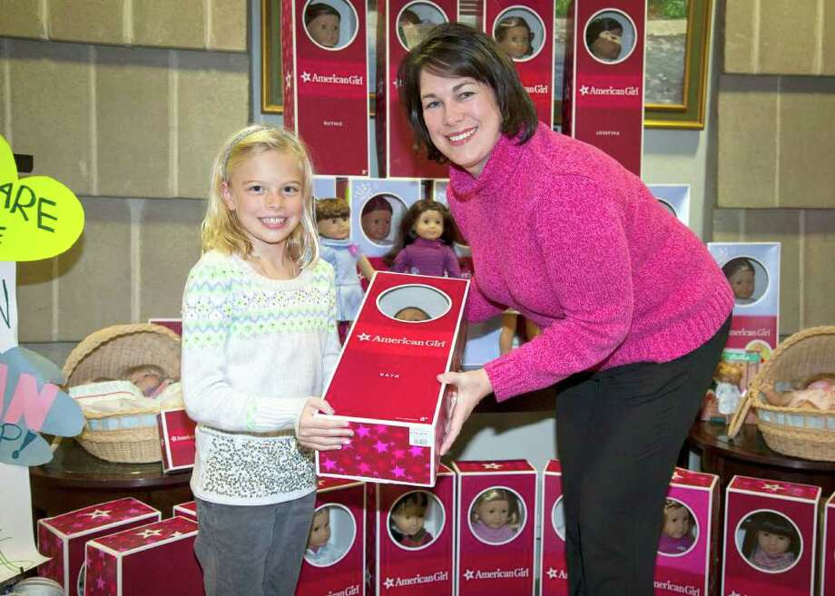 "Greenwich resident Brinkley Blum, 9, presents Suzanne Adam, Director of YWCA Domestic Abuse Services, with 32 American Girl dolls she helped collect for child victims of domestic violence - so they could ""feel better"" around the holidays. Photo: Contributed Photo / Greenwich Citizen"