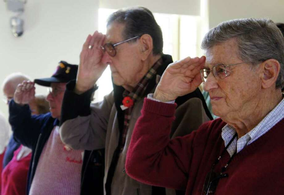 Ed Van Gelder, right, a World War II veteran, salutes the flag during a Veterans Day ceremony held at Westport Town Hall on Friday, Nov. 11, 2011. Photo: Paul Schott / Westport News