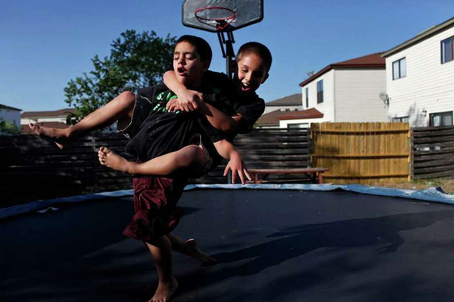 metro - Michael Gaines, 9, right, holds onto his brother, David Gaines, 8, left, as they play on the trampoline at their home on Thursday, Oct. 20, 2011. The brothers and their sister, Alexis Gaines, 7, were born with symptoms of fetal alcohol syndrome and adopted by Yvonne Gaines.  LISA KRANTZ/lkrantz@express-news.net Photo: LISA KRANTZ, SAN ANTONIO EXPRESS-NEWS / SAN ANTONIO EXPRESS-NEWS