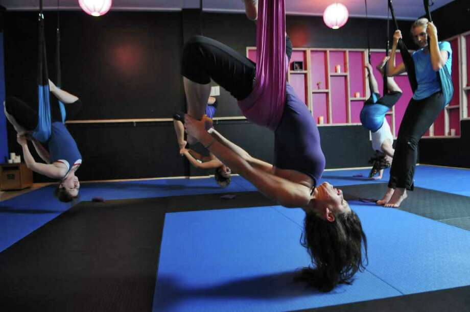 Times Union reporter Kristi Barlette, right, takes a break during a gravity yoga class led by instructor Jessica Lubin, center, at Good Karma Studio on Wednesday night Oct. 19, 2011 in Colonie, NY.  (Philip Kamrass / Times Union ) Photo: Philip Kamrass / 00014977A