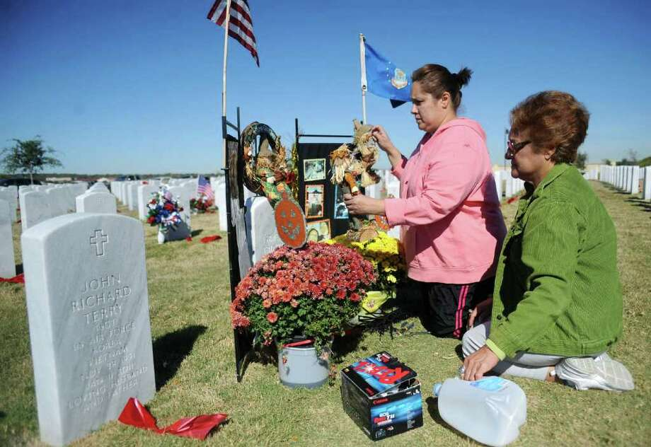 Anselma Trinidad and her daughter, Bianca Reyes, decorate the grave of her husband, Marines and Air Force veteran Israel Trinidad, who died in January. They visited the Fort Sam Houston National Cemetery on Veterans Day, Nov. 11, 2011.  BILLY CALZADA / gcalzada@express-news.net
