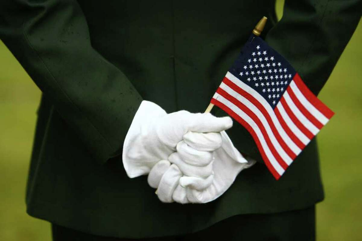 A U.S. Army solider holds a flag during the 62nd Annual Veterans Day Memorial Celebration at Evergreen-Washelli Cemetery on Friday, November 11, 2011.
