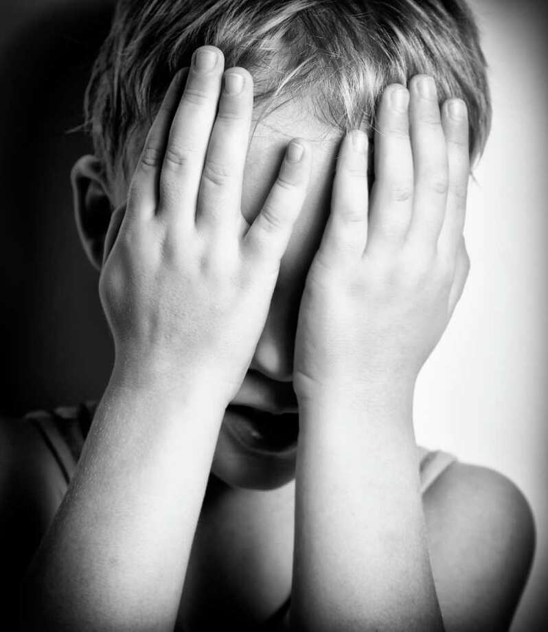 BW portrait of sad crying little boy covers his face with hands FOTOLIA