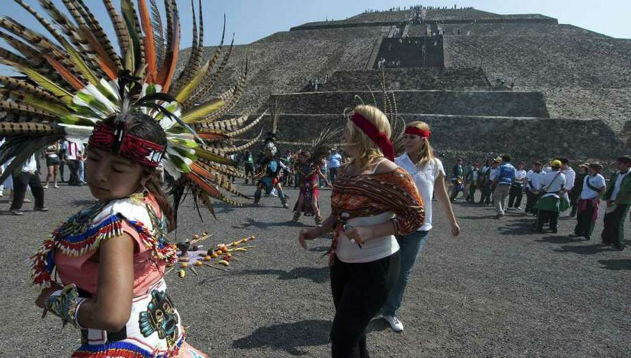 A dancer dressed in Aztec costumes performs next to tourists in front of the Pyramid of Sun in Teotihuacan archaeological site, Mexico State, Mexico on November 11, 2011. People gathered around the pyramids in Teotihuacan seeking for harmony on the date 11/11/11. Photo: OMAR TORRES, Getty / AFP