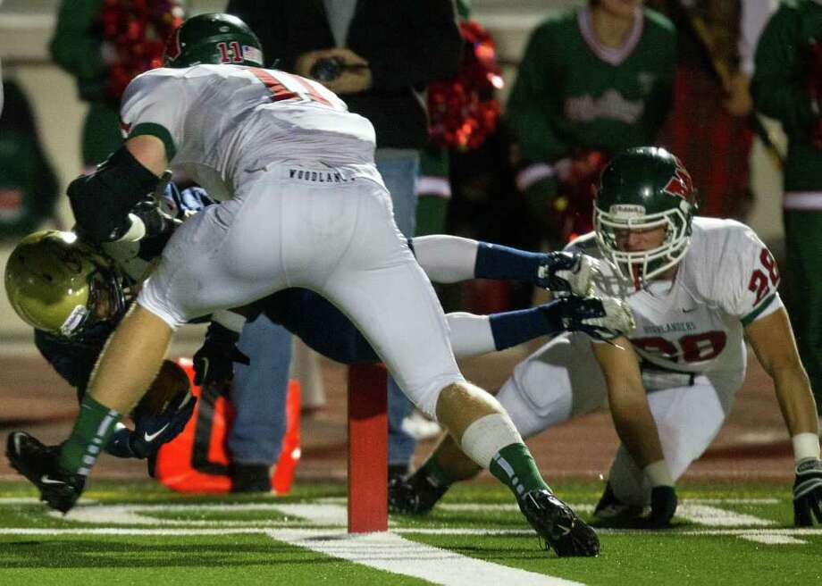 Klein Collins running back Shane Rhodes (4) dives into the end zone for a touchdown past The Woodlands defenders Garrett Hope (11) and Thomas Adams (28) during the first quarter of a high school football playoff game at  Turner Stadium, Friday, Nov. 11, 2011, in Humble. Photo: Smiley N. Pool, Houston Chronicle / © 2011  Houston Chronicle