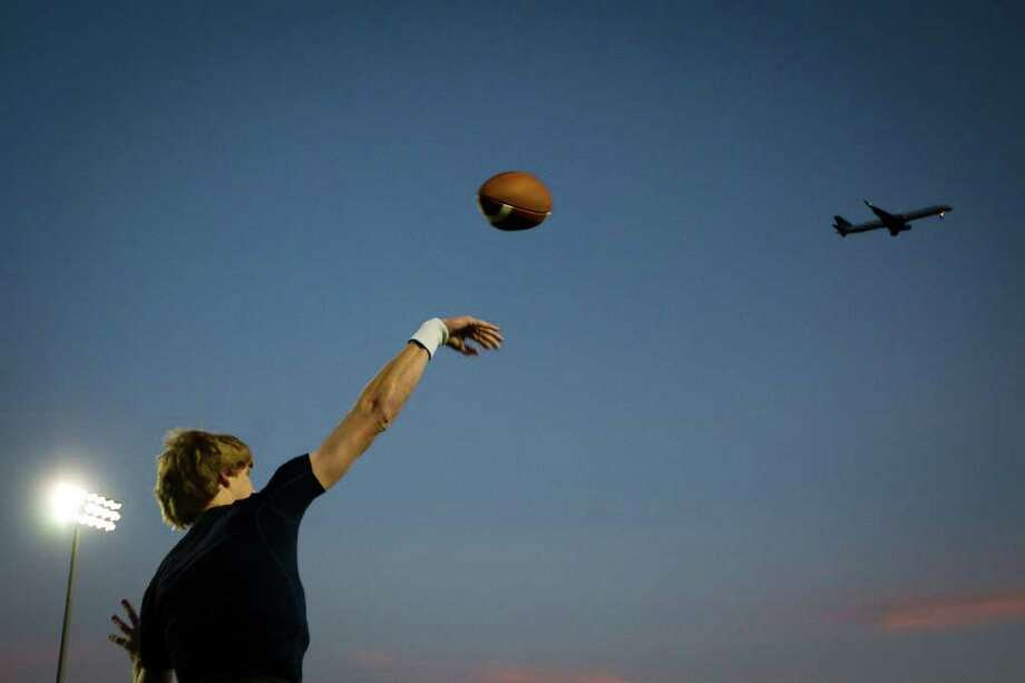 Klein Collins quarterback Tyler Stehling warms up as aircraft on approach to Houston Intercontinental Airport pass overhead before a high school football playoff first-round game against The Woodlands at  Turner Stadium, Friday, Nov. 11, 2011, in Humble. Photo: Smiley N. Pool, Houston Chronicle / © 2011  Houston Chronicle
