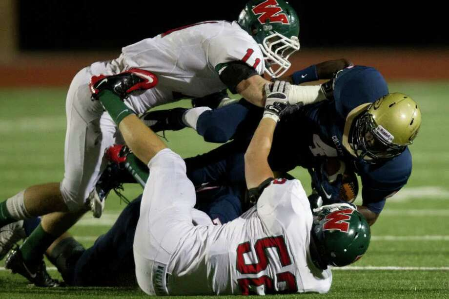 Klein Collins running back Shane Rhodes (4) is brought down by The Woodlands linebackers Garrett Hope (11) and Brandon Taylor (52) during the first quarter of a high school football playoff game at  Turner Stadium, Friday, Nov. 11, 2011, in Humble. Photo: Smiley N. Pool, Houston Chronicle / © 2011  Houston Chronicle