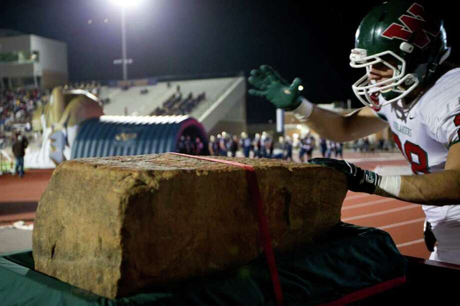 "The Woodlands defensive back Thomas Adams (28) touches ""The Stone of Destiny"" before taking the field to play Klein Collins in a high school football playoff game at  Turner Stadium, Friday, Nov. 11, 2011, in Humble. Photo: Smiley N. Pool, Houston Chronicle / © 2011  Houston Chronicle"