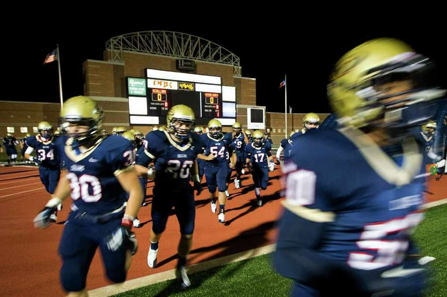 Klein Collins players race onto the field to warm up before facing The Woodlands in a high school football playoff game at Turner Stadium, Friday, Nov. 11, 2011, in Humble. Photo: Smiley N. Pool, Houston Chronicle / © 2011  Houston Chronicle
