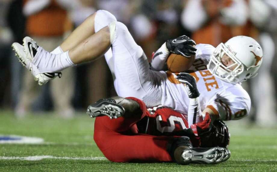 Dobie's Dominique Bilbo (5) is brought down after a reception by North Shore's Kevin Alexander during the first half of a high school football playoff game, Friday, November 11, 2011 at Galena Park Stadium in Houston. Photo: Eric Christian Smith, For The Chronicle