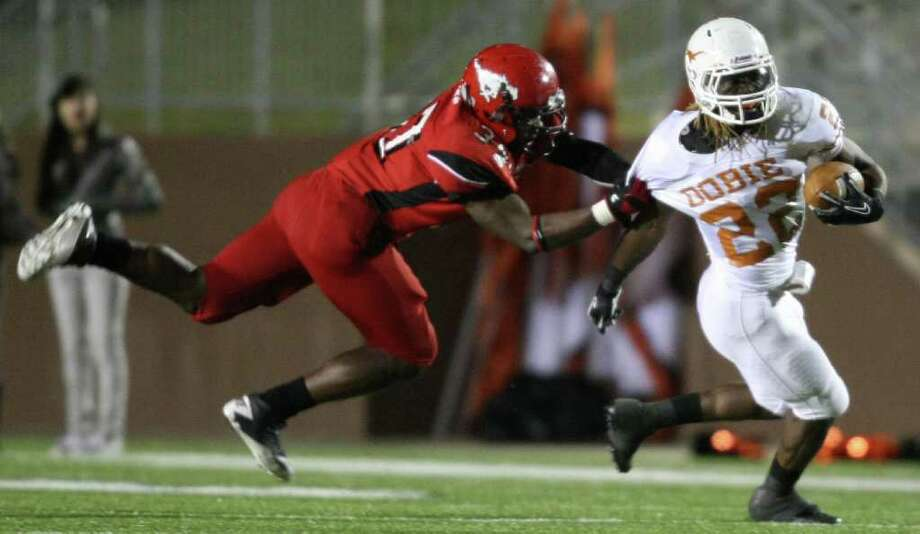 Dobie's Andrew Robinson (right) is tackled by North Shore's Jarius Moore during the first half of a high school football playoff game, Friday, November 11, 2011 at Galena Park Stadium in Houston. Photo: Eric Christian Smith, For The Chronicle