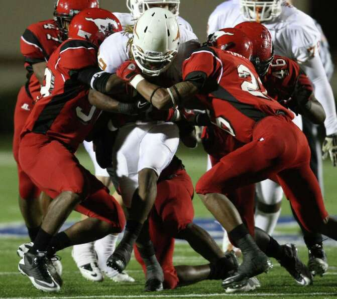 Dobie's Andrew Robinson (22) is tackled by North Shore's Corey Collins (left) and Keon Harvison duri