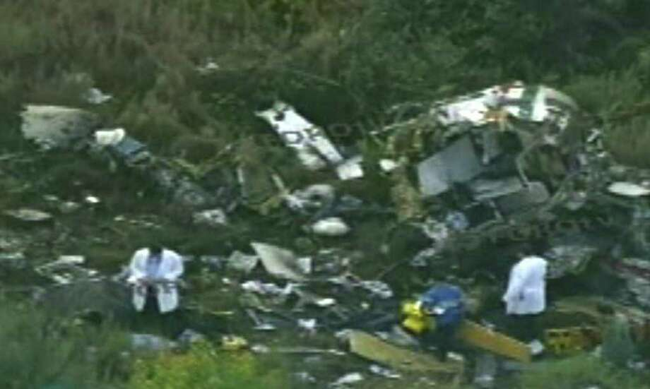 In this video frame grab image taken from Televisa's Forotv via APTN, investigators examine the wreckage of a helicopter that was carrying Mexico's Interior Minister Francisco Blake Mora, in a mountainous area of Mexico state southeast of Mexico City, Friday Nov. 11, 2011. The Mexican government said Friday, that Mora, Mexico's No. 2 government official next to the president, died in the helicopter crash with seven others, including the pilot. (AP Photo/Forotv-Televisa via APTN) / Forotv-Televisa via APTN
