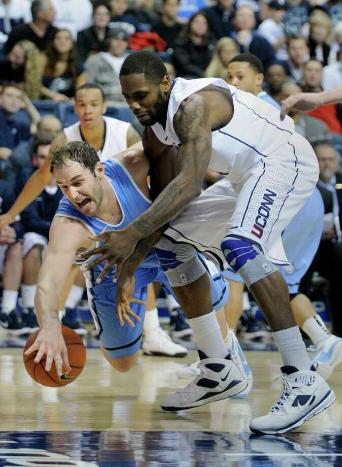 Columbia's Mark Cisco, left, fights for a loose ball with Connecticut's Alex Oriakhi during the second half of their NCAA college basketball game in Storrs, Conn., on Friday, Nov. 11, 2011. Connecticut won the game 70-57. (AP Photo/Fred Beckham) Photo: Fred Beckham/Associated Press / FR153656 AP
