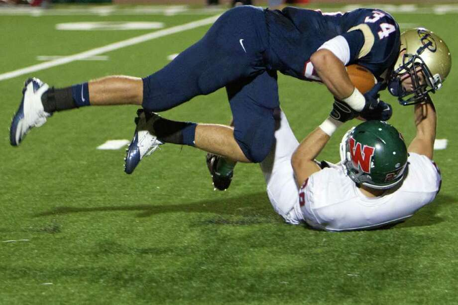 Klein Collins running back Marcus Goodson (3) is brought down by The Woodlands defensive back Thomas Adams (28) during the second quarter of a high school football playoff game at  Turner Stadium, Friday, Nov. 11, 2011, in Humble. Photo: Smiley N. Pool, Houston Chronicle / © 2011  Houston Chronicle