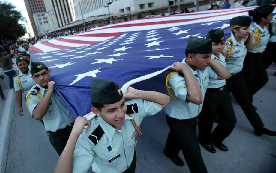 "JH Reagan HS ROTC carries the U.S. Flag during Veterans Day Parade along Smith St. on Friday, Nov. 11, 2011, in Houston.    ""Houston Salutes American Heroes"" festivities include the AT&T Veteran Job Fair and the Walgreens Veterans Health Fair. Photo: Mayra Beltran, Houston Chronicle / © 2011 Houston Chronicle"