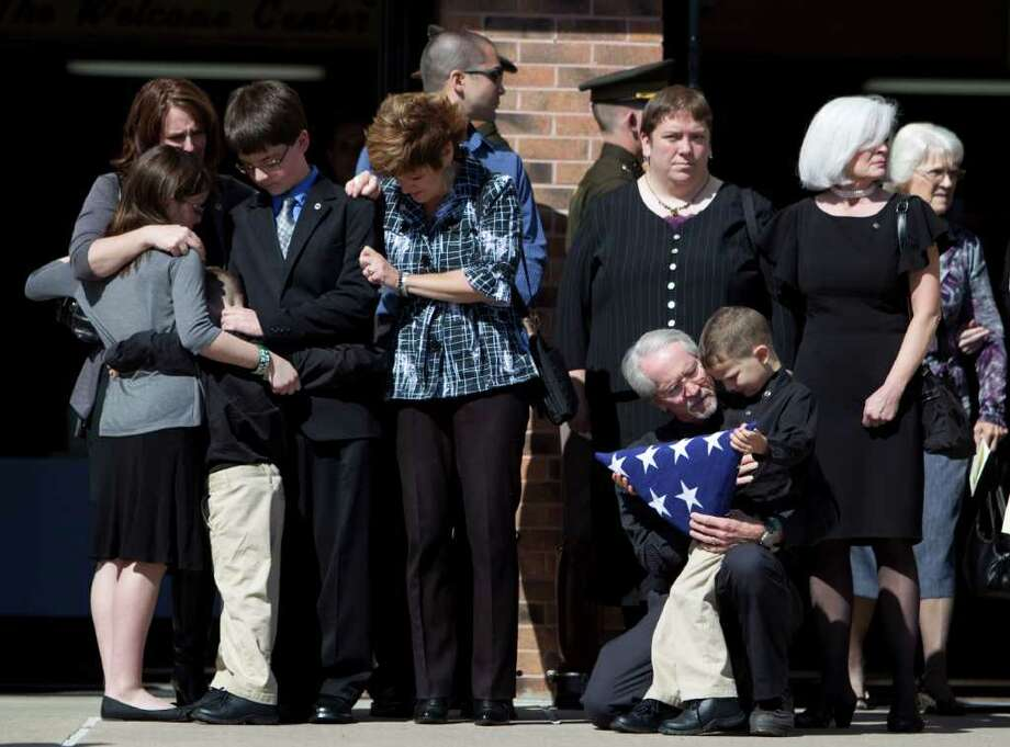 Cabrera's son Roanin, 5, is comforted by his grandfather, Michael Wegener, right, while Gillian, 12, Maxwell, 7, and Corbin, 13, are consoled by other family members after their father's funeral Friday at Spring Baptist Church. Photo: Johnny Hanson / © 2011 Houston Chronicle
