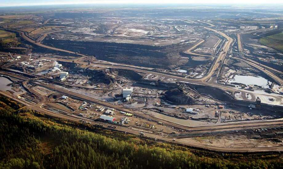 FILE - This Sept. 19, 2011, aerial photo shows a tar sands mine facility near Fort McMurray, in Alberta, Canada. The White House plan to seek alternate routes for a Canada-to-Texas oil pipeline presents a tangle of new problems for the project's backers, and any of those obstacles could still sink the proposal before the first spade of dirt is turned. Shifting the path to avoid a major aquifer could increase the number of perilous stream crossings and put the line closer to populated areas.(AP Photo/The Canadian Press, Jeff McIntosh, File) Photo: Jeff McIntosh / THE CANADIAN PRESS