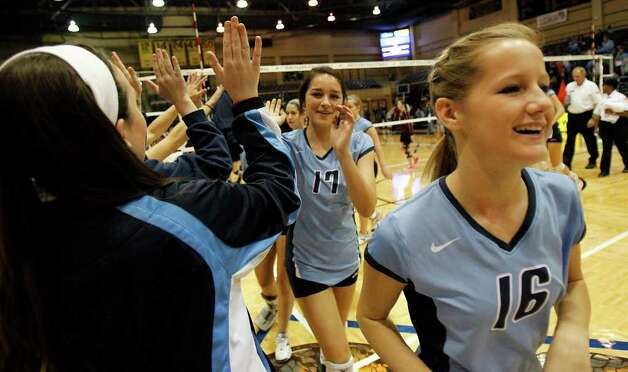 Johnson's Shelby Walker, center, and Alex Yarbrough, right, celebrate with their team after a win against Los Fresnos during the Region IV-5A volleyball semifinals at Greehey Arena at St. Mary's University on Friday, Nov. 11, 2011. Johnson won in straight sets (25-12, 25-15, 25-14). MICHAEL MILLER / mmiller@express-news.net Photo: MICHAEL MILLER, Express-News / mmiller@express-news.net