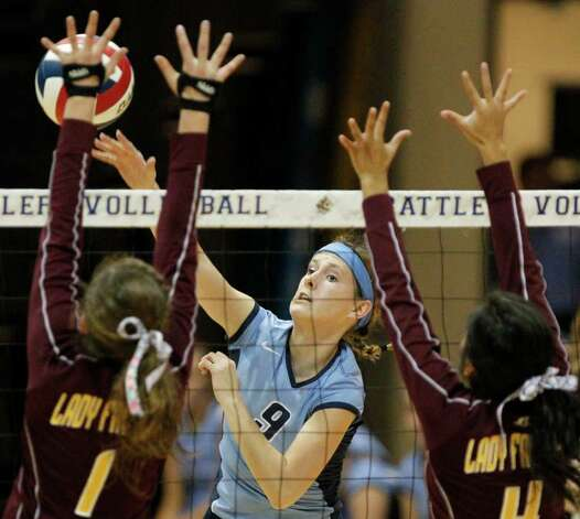 Johnson's Kassie Freitag, center, spikes the ball against the defense of Los Fresnos' Hayley Weaver, left, and Stephanie Shears, right, during the Region IV-5A volleyball semifinals at Greehey Arena at St. Mary's University on Friday, Nov. 11, 2011. Johnson won in straight sets (25-12, 25-15, 25-14). MICHAEL MILLER / mmiller@express-news.net Photo: MICHAEL MILLER, Express-News / mmiller@express-news.net