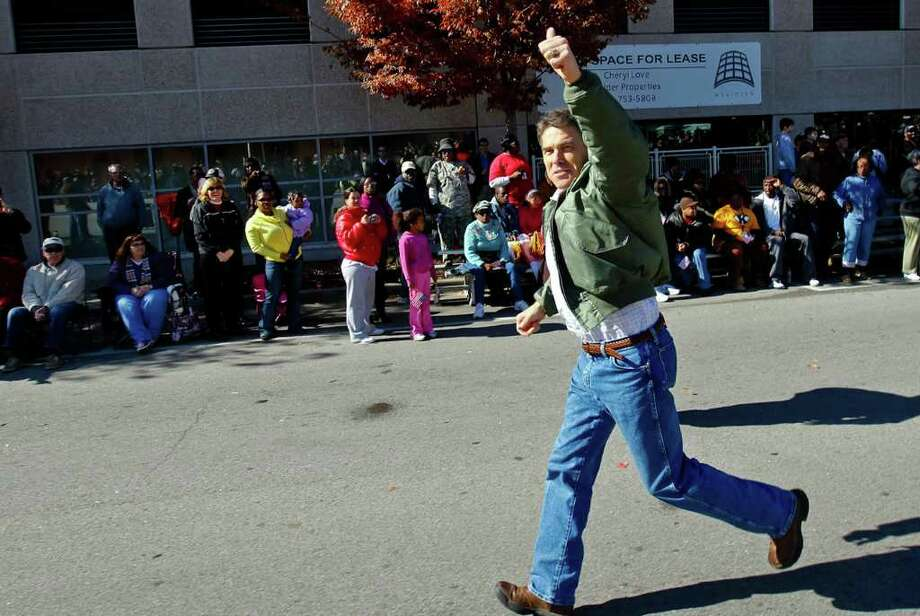 Republican presidential candidate Rick Perry waves during a Veterans Day parade in Columbia, S.C., on Friday, Nov. 11, 2011. Fellow Republican candidate Michelle Bachmann also marched in the parade. (AP Photo/The State, Tim Dominick) Photo: Tim Dominick