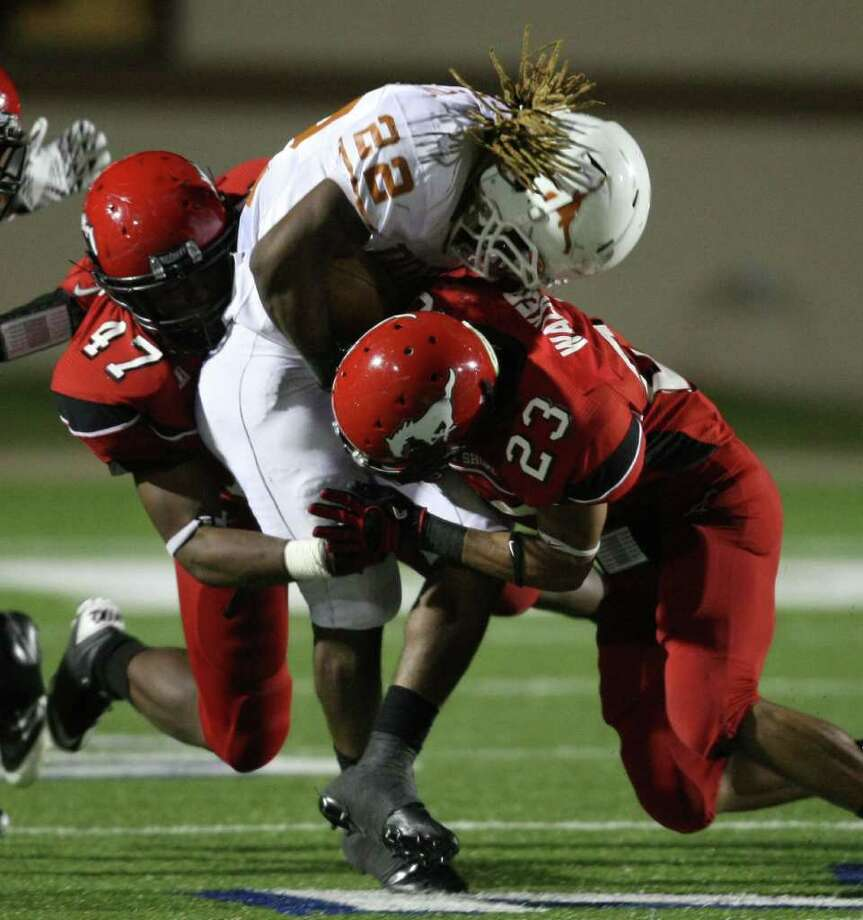 Dobie's Andrew Robinson, center, is taken down by North Shore's Troy Roach, left, and Jacoby Walker during the second half Friday night. Photo: Eric Christian Smith