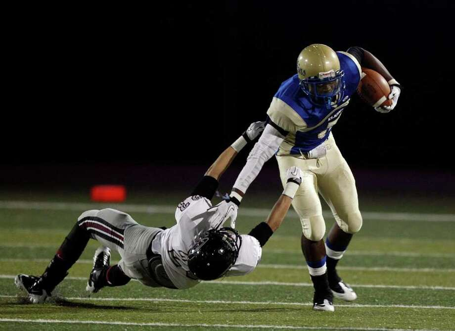 Elkins running back JaWuan Rogers #5 avoids a tackle by Pearland's Derek Hutchinson #$23 during a first round playoff game between the Pearland Oilers and Elkins Knights Friday, November 11, 2011 in Alvin, Texas. Photo: Bob Levey / ©2011 Bob Levey