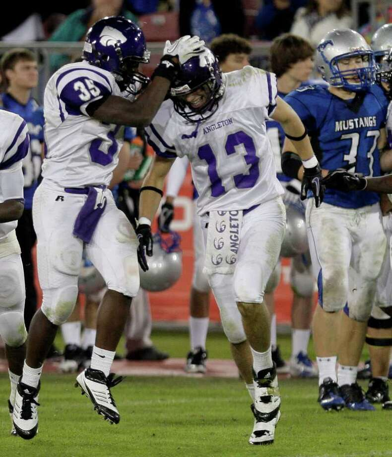 Angleton 48, Friendswood 21.Cornerback Dillon Shugart (13) is congratulated by corner back Javarius Robinson (35) of the Angleton Wildcats after intercepting a Friendswood Mustangs pass while playing in the second half. Photo: Thomas B. Shea / © 2011 Thomas B. Shea