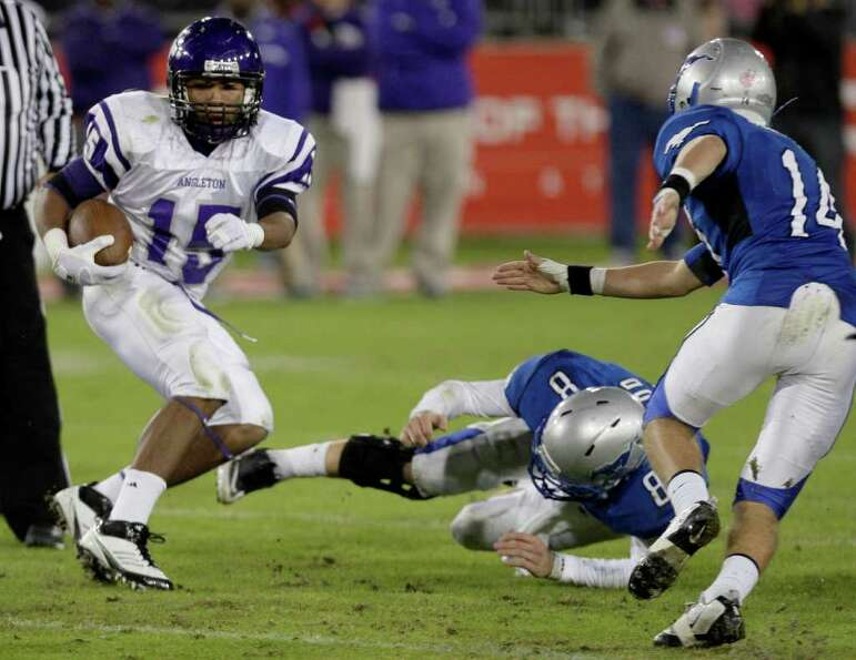 Running back Richard Cooper (15) of the Angleton Wildcats spins and breaks the tackle of defensive b