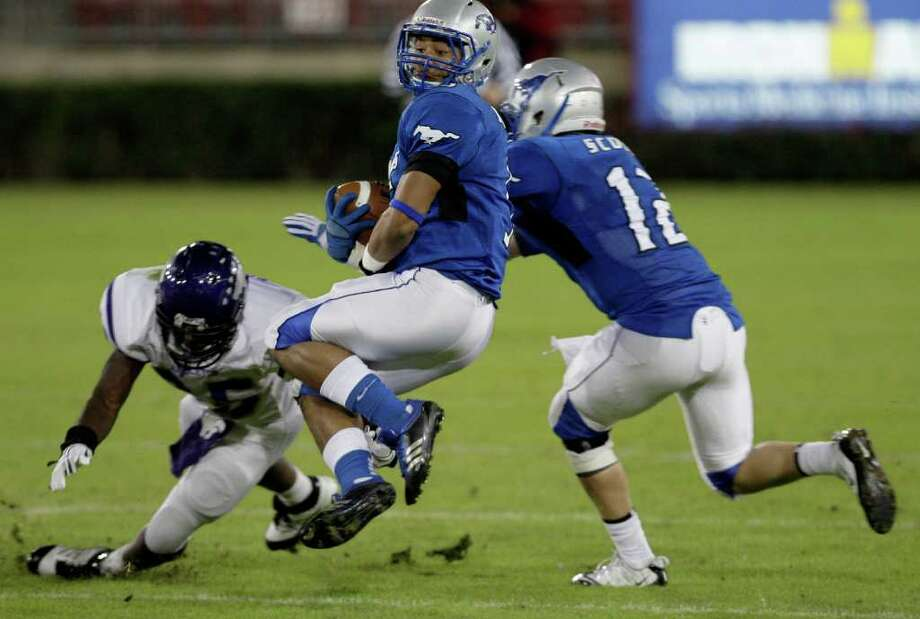 Running back Hudson Stock (15) of the Friendswood Mustangs spins and gains 64 yards on the rush against the Angleton Wildcats  while playing in the first half of a playoff high school football game on November 11, 2011 at Robertson Stadium in Houston, Texas. Photo: Thomas B. Shea / © 2011 Thomas B. Shea
